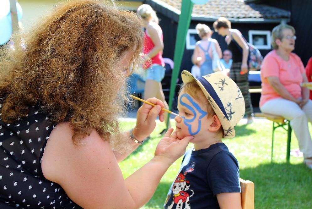 Betreuungsperson bemalt das Gesicht eines Kindes