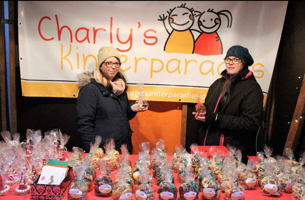 Mitarbeiter des Charly's Kinderparadies präsentieren Kekse in der Weihnachtsmarkt Bude