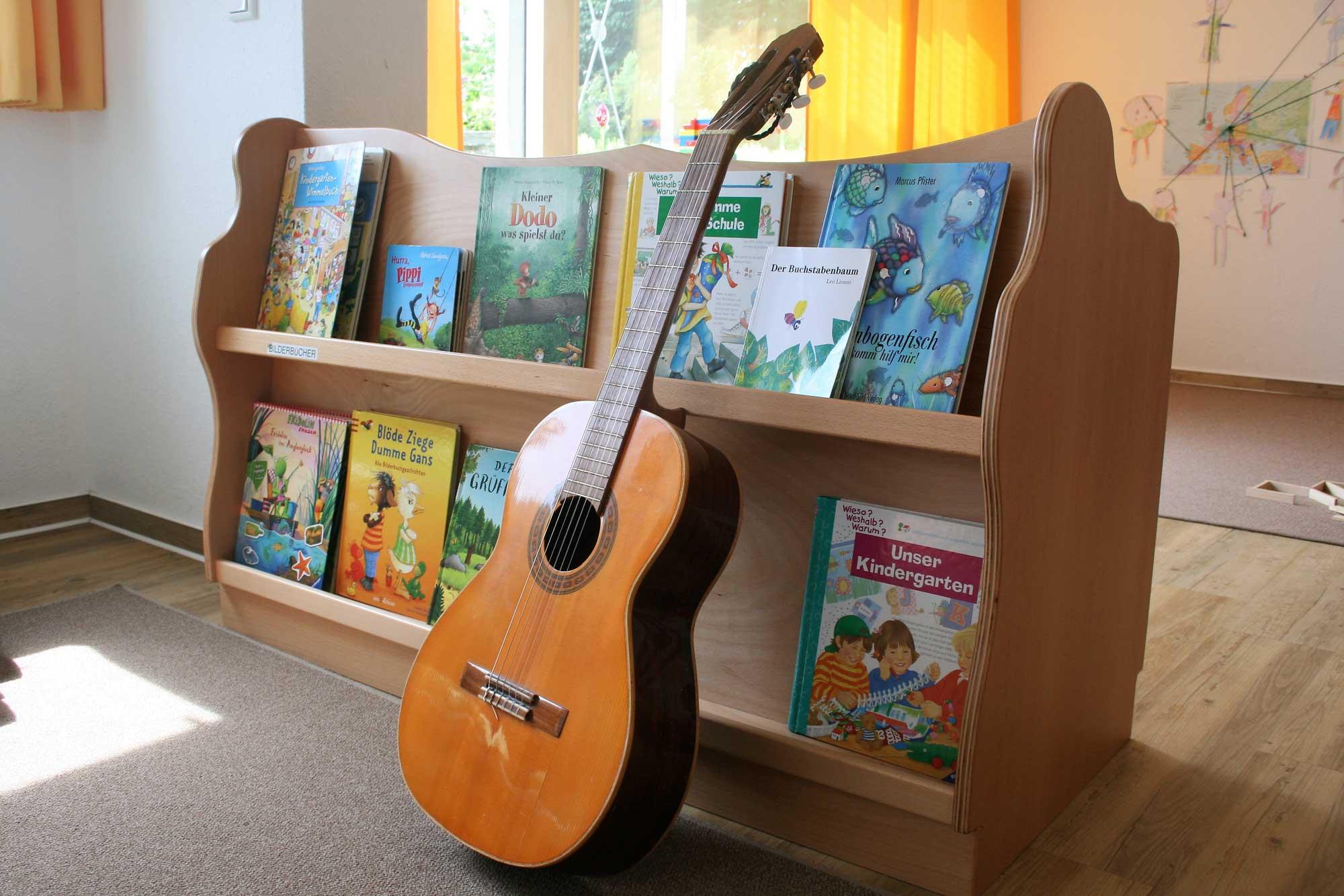 Bücherregal mit Büchern und Gitarre davor