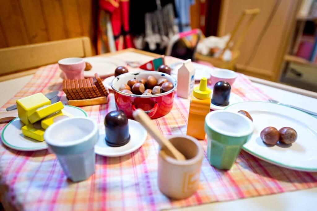Ein Spielzeugtisch zum Essen eingedeckt mit Spielzeug und Nüssen