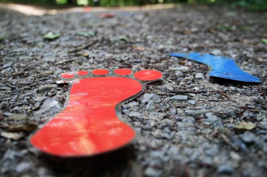 Ausgeschnittene Fußabdrücke auf Kiesboden