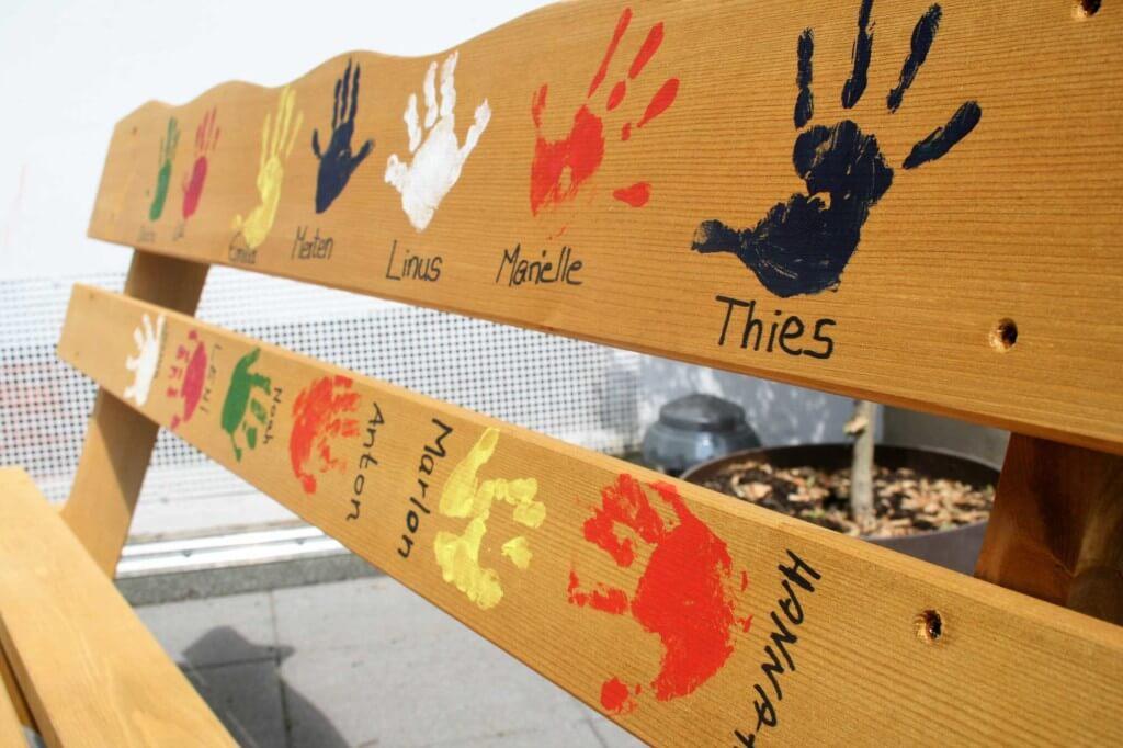 Nahaufnahme einer Sitzbank mit Handabdrücken und Namen der Kinder