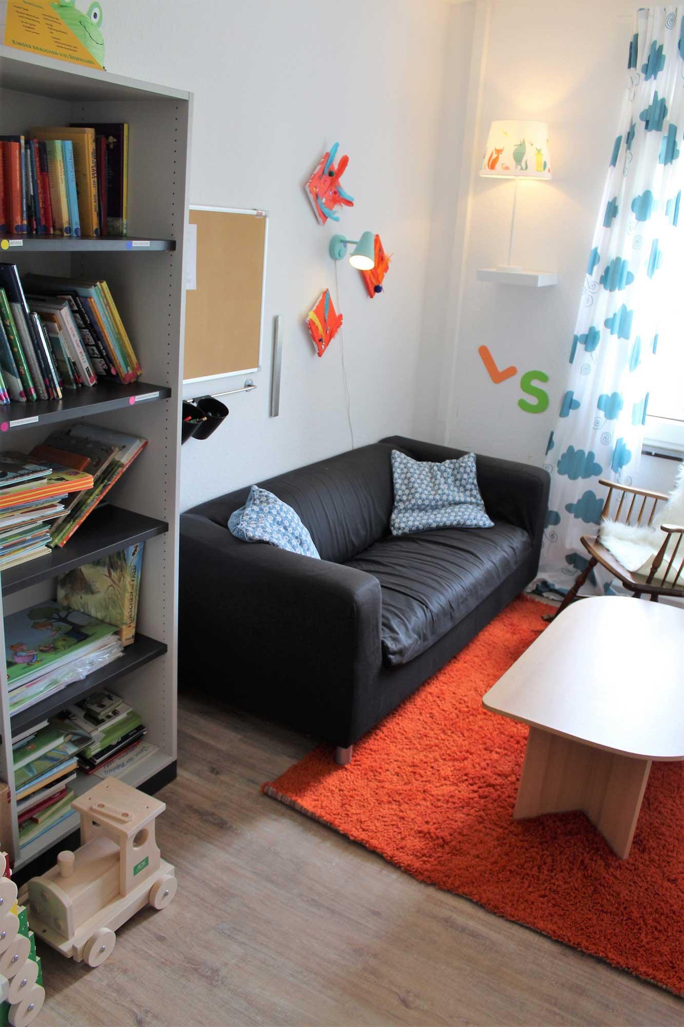 Eine Leseecke mit Sofa und Schaukelstuhl und gefülltem Bücherregal
