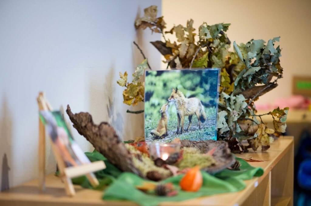 Ein Regal im Thema Herbst mit Blättern, Rinde und Fuchsbildern dekoriert
