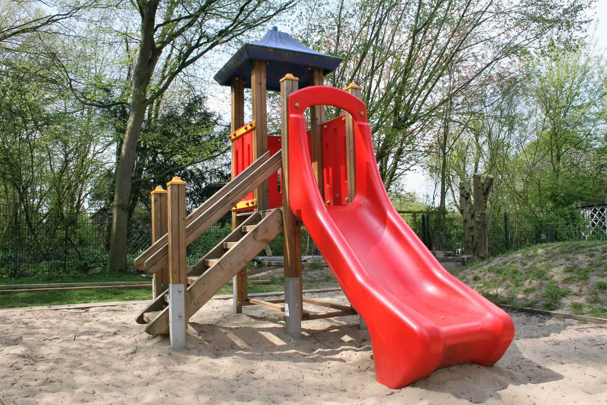 Außenaufnahme des Spielplatzes mit Kletterturm und großer, roter Rutsche