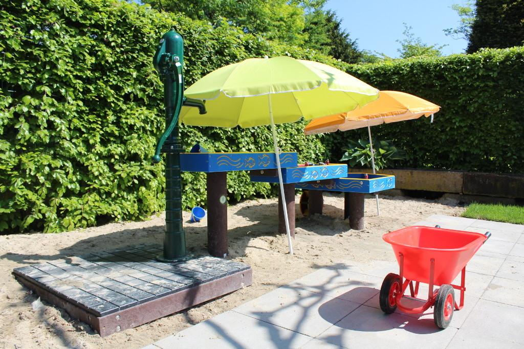 Ein Wasserpumpspiel im Sommer mit Sonnenschirmen geschützt