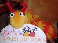 Ein Plüschtier hält ein Charly's Kinderparadies Logo im Mund