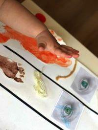 eine Kinderhand über gestalteten Bildern