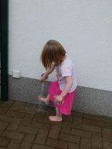 Ein Kindergartenkind spült sich die Füße am Wasserhahn außen ab