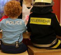 Als Feuerwehrmann und Polizist verkleidete Kinder sitzen mit dem Rücken zur Kamera