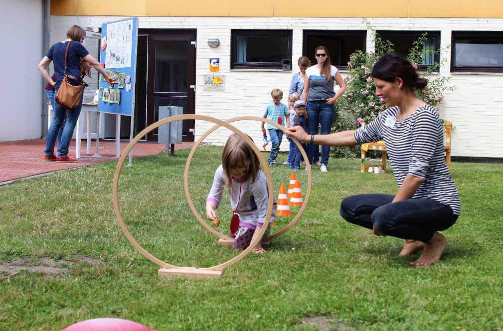 Ein Mädchen krabbelt beim Eierlauf durch Ringe
