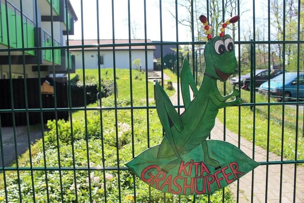 Zaun mit Schild eines Grashüpfers