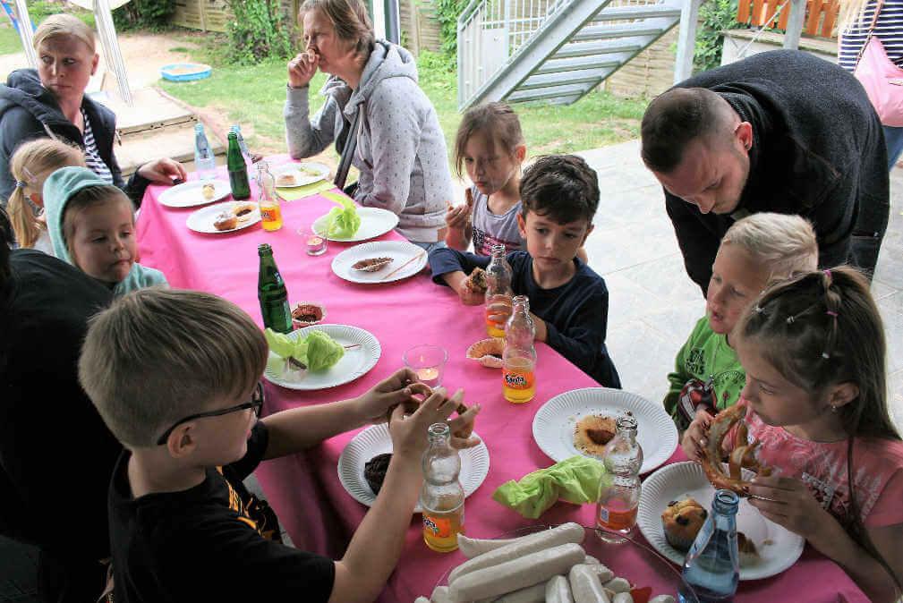 Kindergartenkinder essen mit Erwachsenen draußen an Bierzeltgarnituren