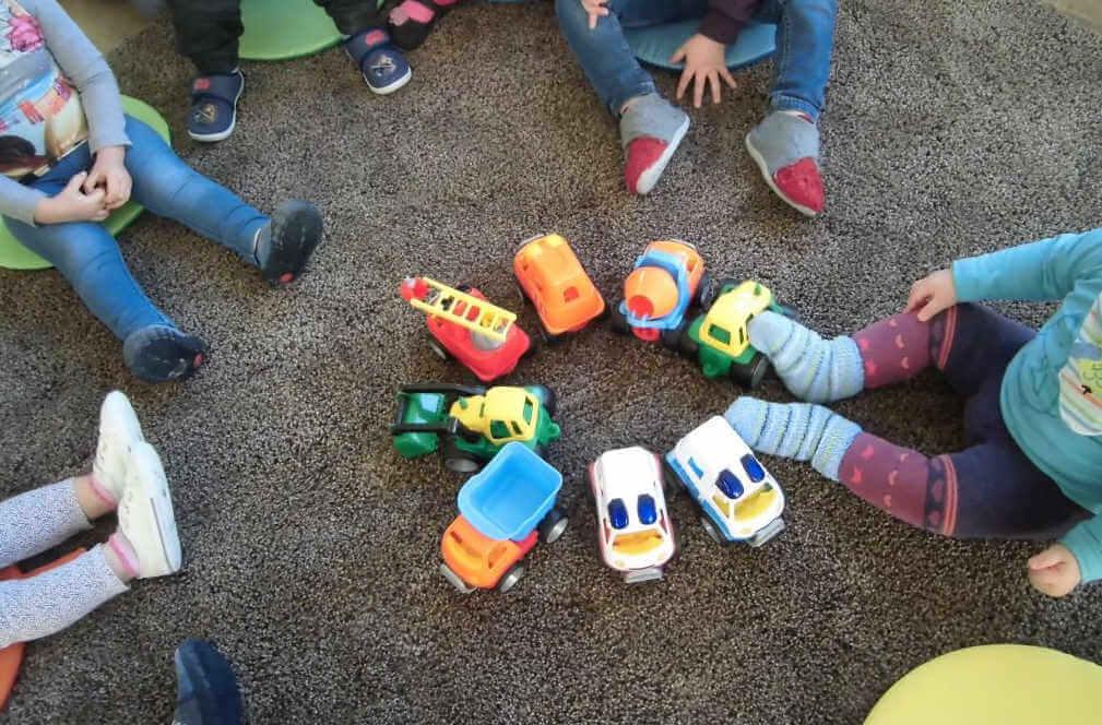 Krippenkinder sitzen im Kreis um neue Spielsachen