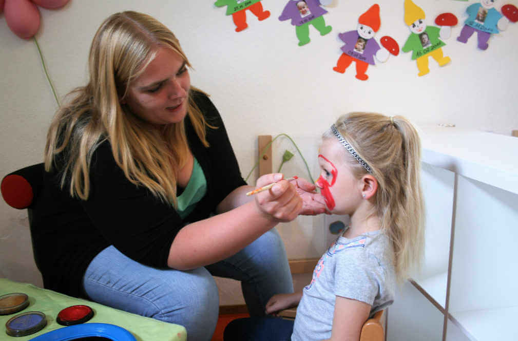 Eine Betreuungsperson bemalt das Gesicht eines Mädchens