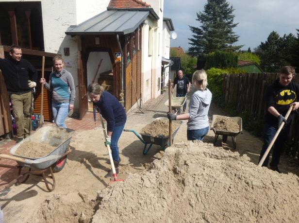 Helfer schaufeln Sand in Schubkarren