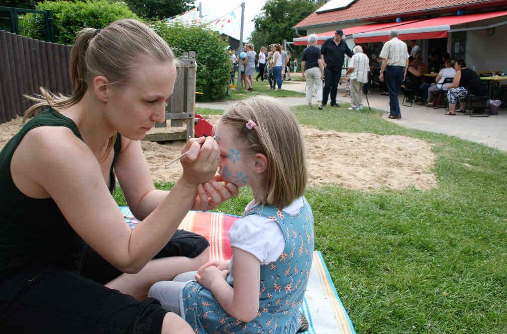 Betreuungsperson schminkt ein Kindergartenkind