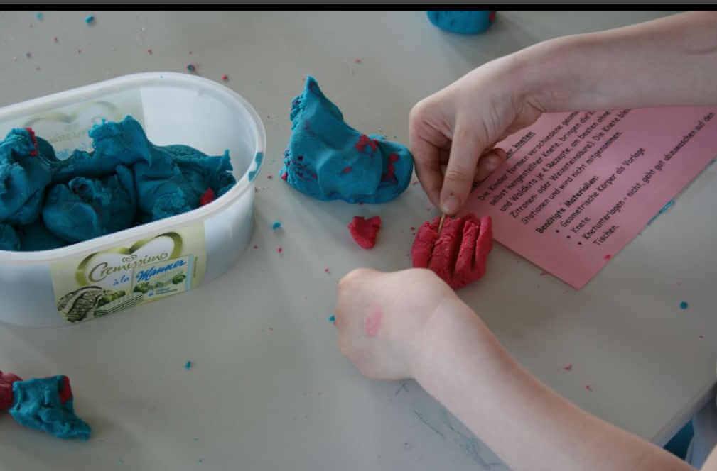 Eine Frau knetet rote Knete