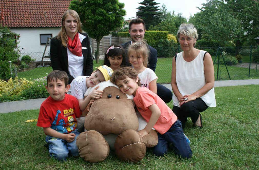 Gruppenfoto von Kindergartenkindern und Erwachsenen mit einem großen Plüschschaf