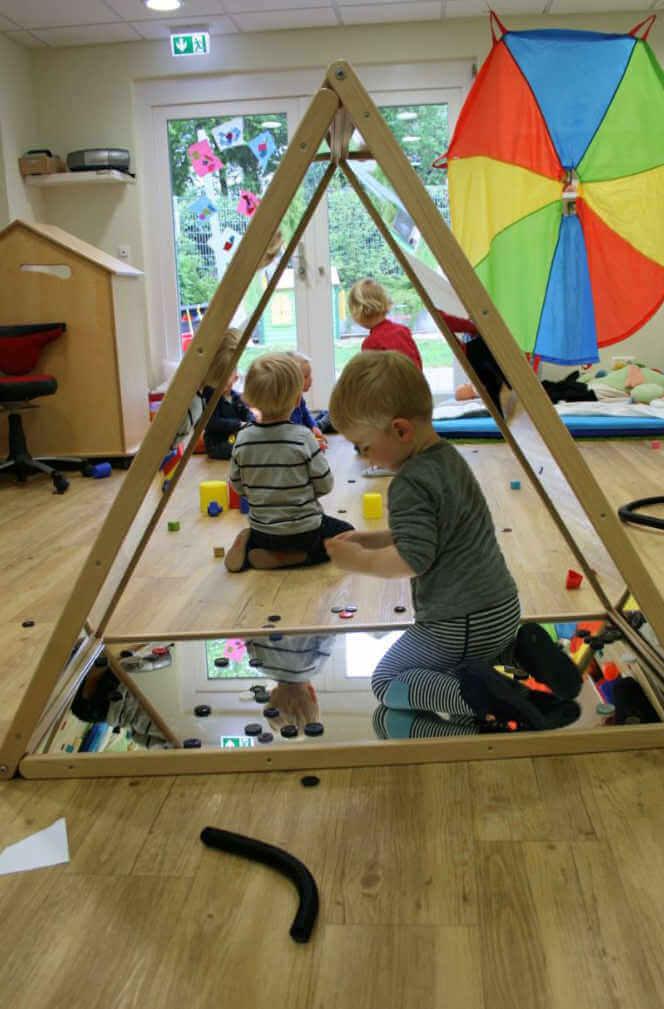 Kinder spielen im Betreuungsraum und ein Junge sitzt im Spiegeldreieck