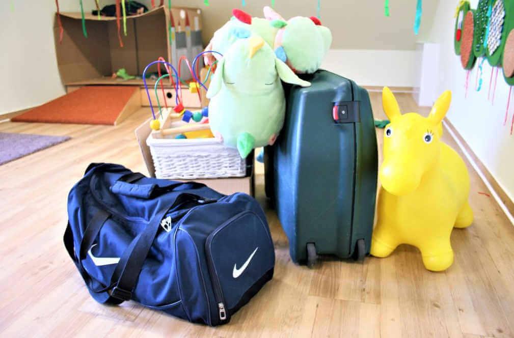 Die Spielsachen des Kindergartens in Koffer und Taschen gepackt gehen auf eine Reise