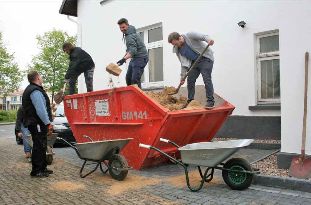 Väter schaufeln Sand aus einem Container in Schubkarren