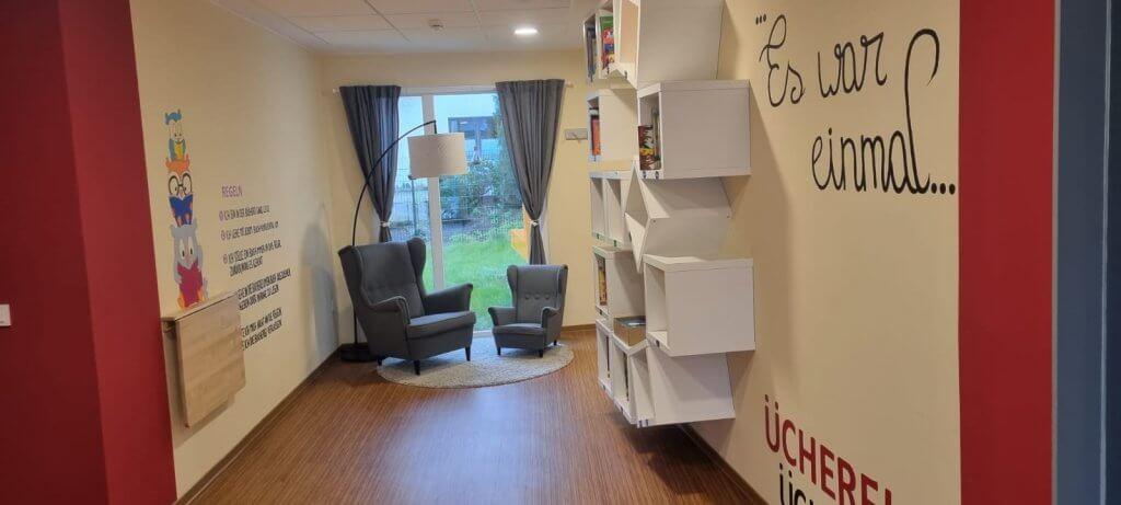 Leseecke mit Lehnsesseln in groß und klein und Bücherragalen an der Wand