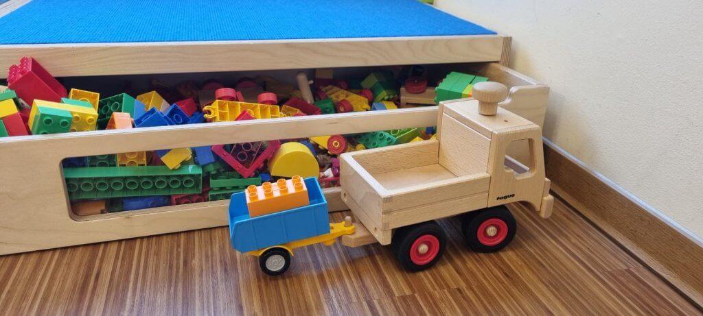 Eine Baukiste voller Lego Duplo Steine mit einem Holzfahrzeug davor