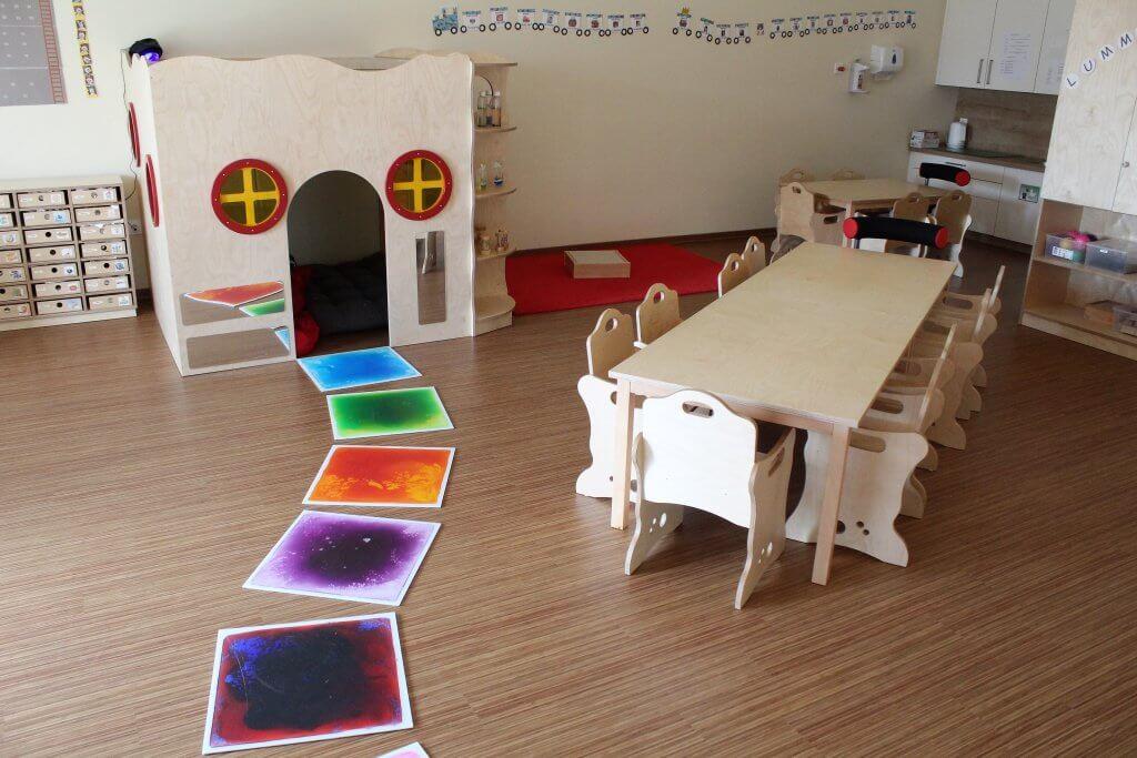 Kindergartenraum mit Tischen und Stühlen, Sensorikmatten und Spielhöhle