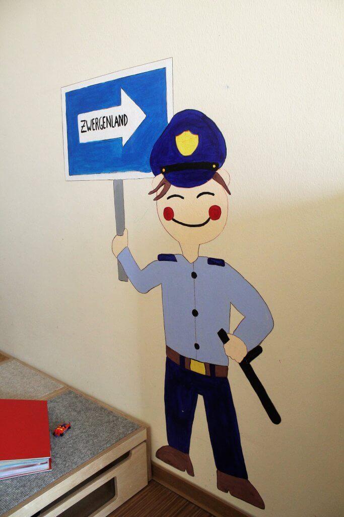 Ein Wandbild eines Polizisten mit Wegweiser zum Zwergenland