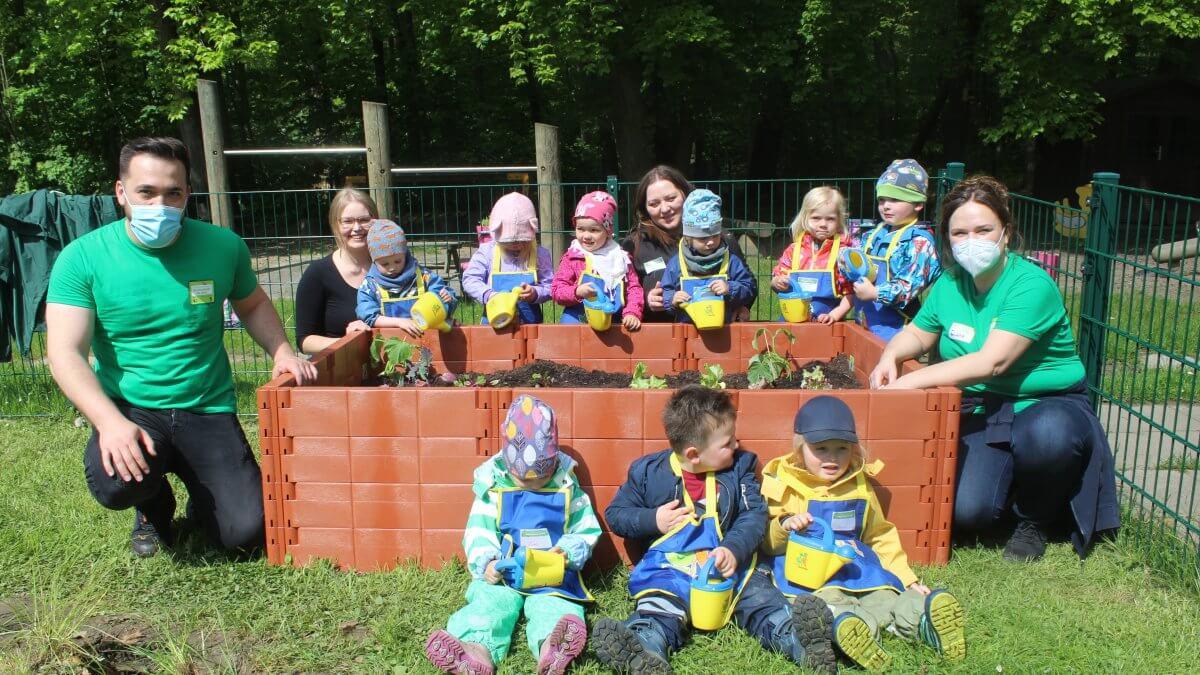 Kindergartenkinder und Betreuer bepflanzen ein Hochbeet