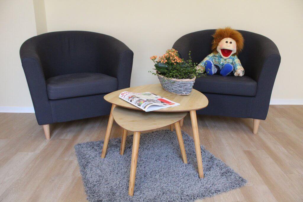 Ein Sitzbereich mit einer Sprechpuppe auf einem der Plätze