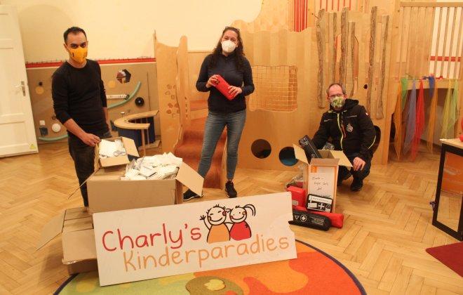 Drei Personen stehen im Krippenraum mit Hilfgütern vom Charly's Kinderparadies
